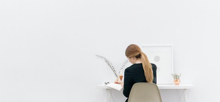 Girl working at desk in white room